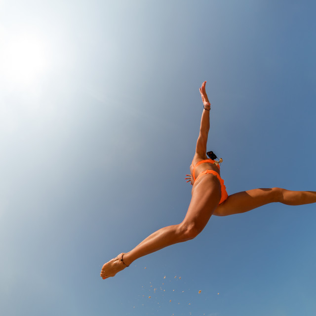 """""""Carefree woman in bikini jumping on the beach with arms outstret"""" stock image"""