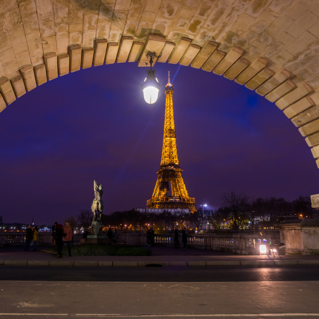 """PARIS - DECEMBER 04 2017: The illuminated Eiffel Tower from the bridge Pont de Bir-Hakeim in Paris France.The Eiffel tower is most visited monument of France with 6 million visitors every year"" stock image"