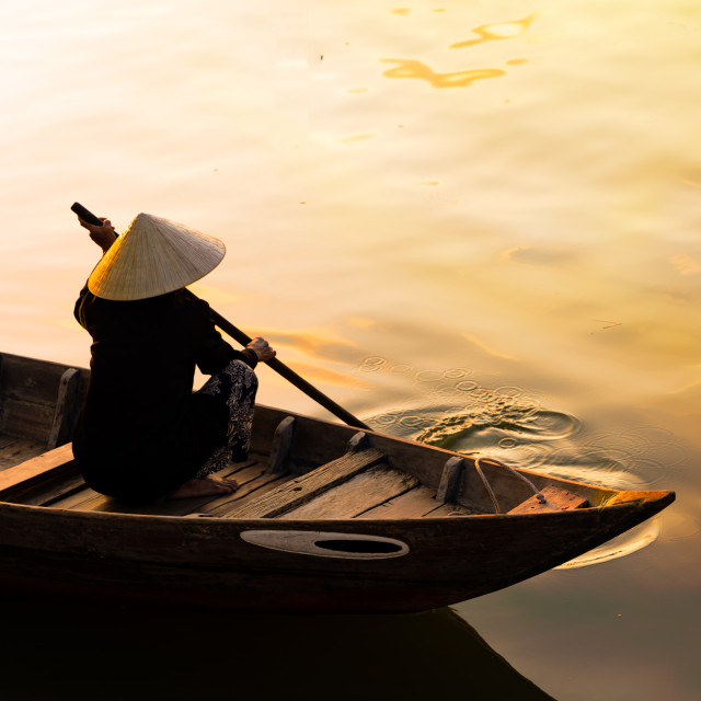 """""""Vietnamese woman in traditional bamboo hat rowing"""" stock image"""