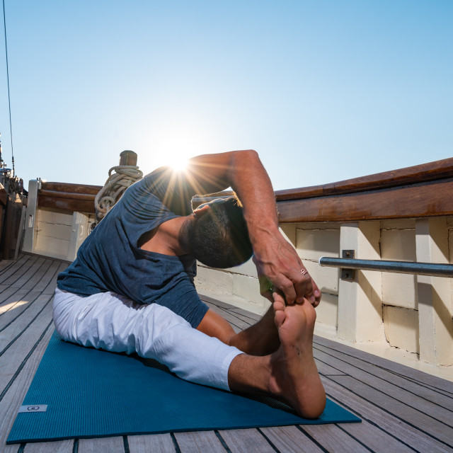 """""""Man practicing Yoga on a sailing yacht"""" stock image"""