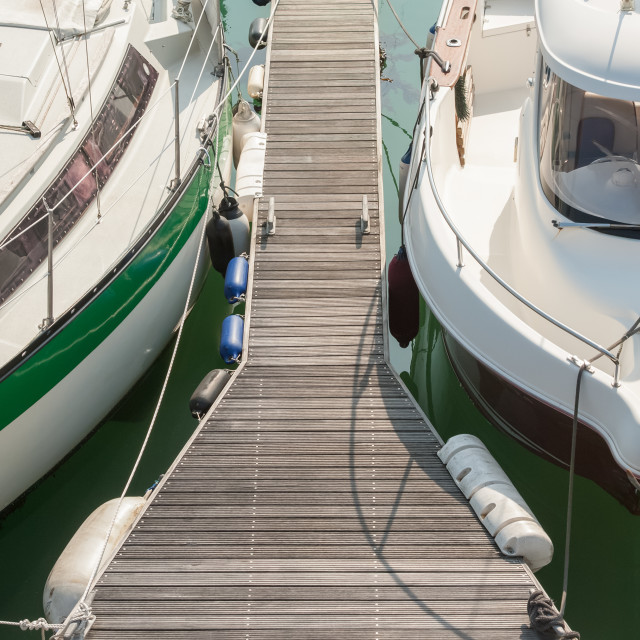 """small boats moored on a jetty"" stock image"