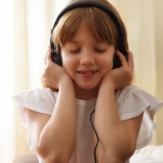 """""""Concentrated girl listening to music carefully holding earphones in livingroom"""" stock image"""