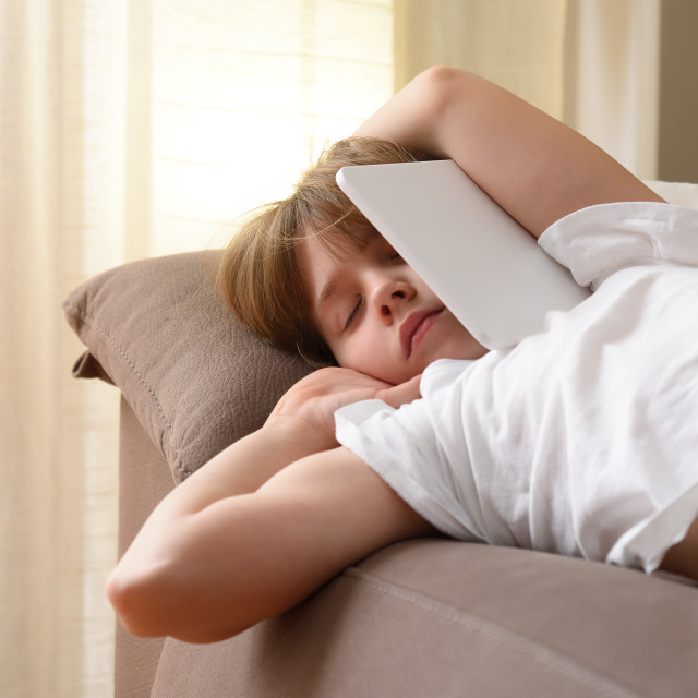 """""""Detail of girl sleeping on sofa with tablet in arms"""" stock image"""
