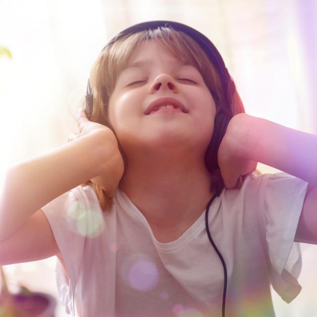 """Girl listening to music carefully holding earphones colored lights"" stock image"