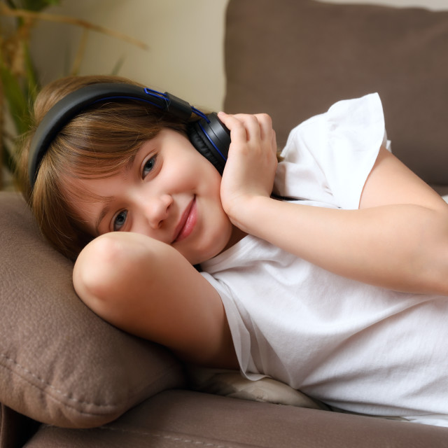 """""""Girl listening to music carefully lying on the sofa at home"""" stock image"""