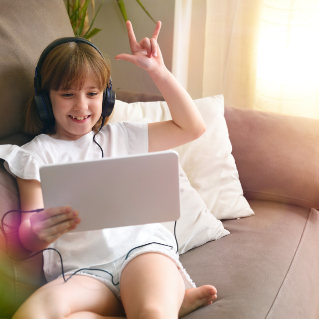 """""""Girl watching and listening hard music videos on tablet headphones"""" stock image"""