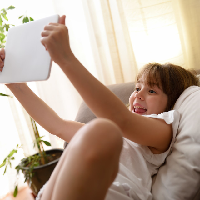"""""""Happy girl sitting on sofa talking on videoconference on tablet"""" stock image"""