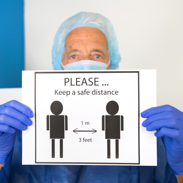 """Doctor with face mask asking for safe distance"" stock image"