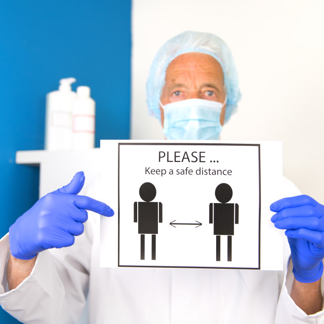 """""""Doctor with face mask asking for safe distance"""" stock image"""