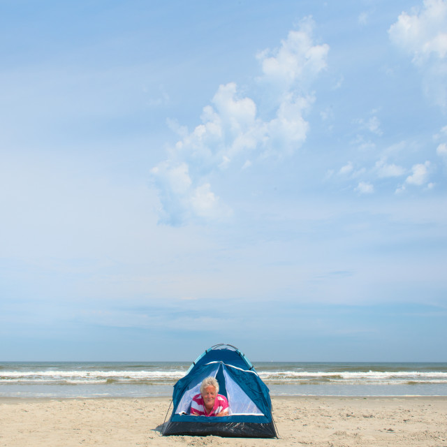 """""""Man camping in shelter at the beach"""" stock image"""