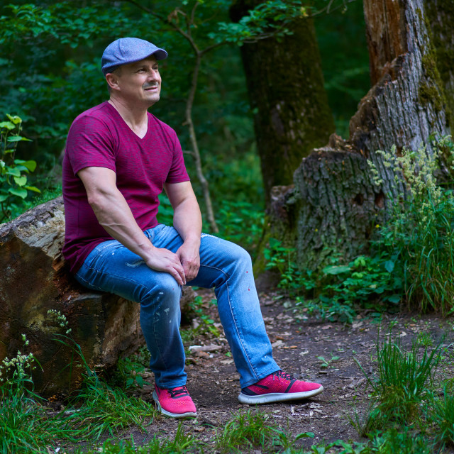 """""""Man sitting on a tree trunk"""" stock image"""