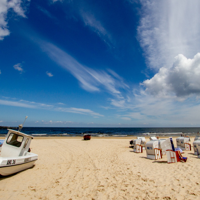 """""""Photographs of Ahlbeck a Seaside Resort on the Baltic Sea Coast, Germany. The Beach with Wicker Sun Shelters on a Sunny Day. Fishing boat to side,"""" stock image"""