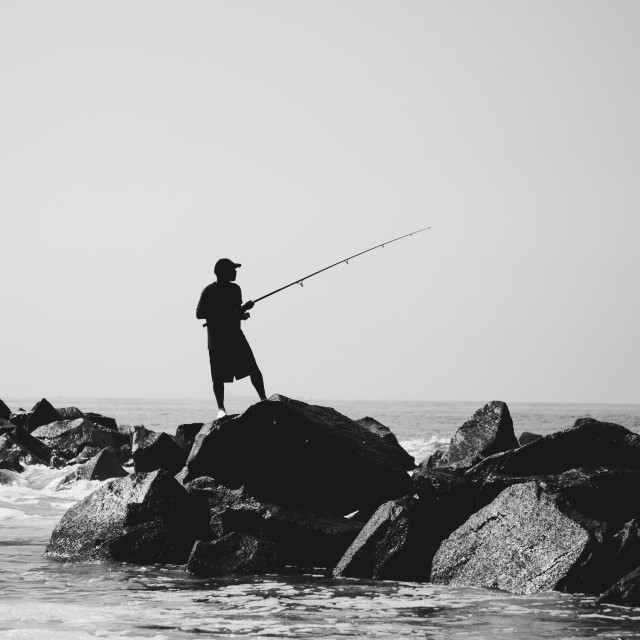 """Fishing Silhouette on Rocks, Venice Beach, Los Angeles, California"" stock image"