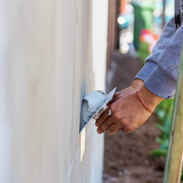 """""""Construction worker plastering cement on wall."""" stock image"""