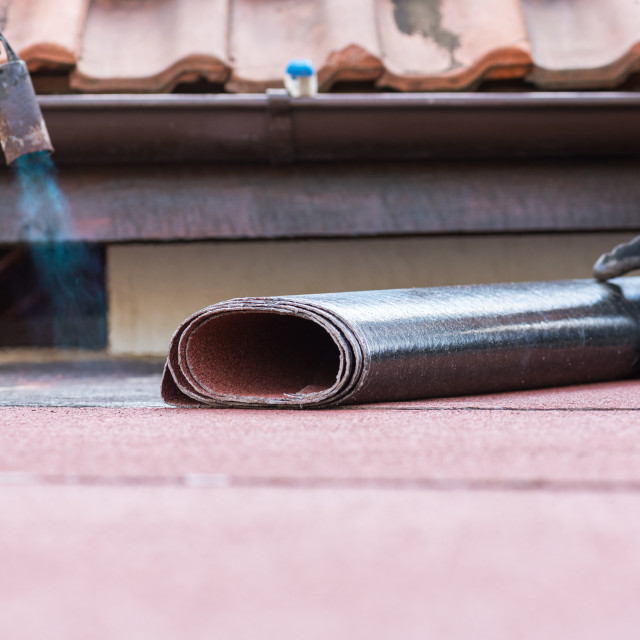 """""""Laying of roofing felt from the roll with a flame from the burne"""" stock image"""