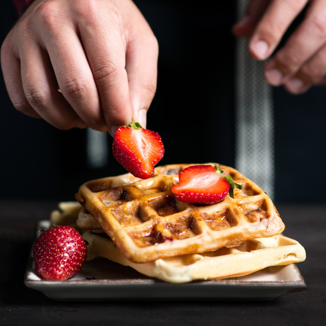 """""""Chef adding strawberries on a waffle close up"""" stock image"""