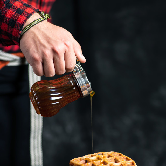 """Man adding honey on a waffle dessert"" stock image"