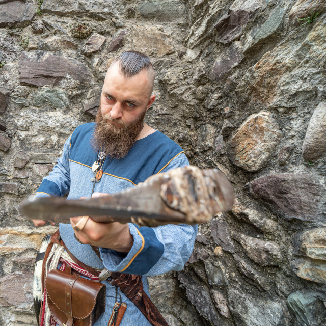 """""""Portrait of a young Viking brandishing an ax in front of a stone"""" stock image"""