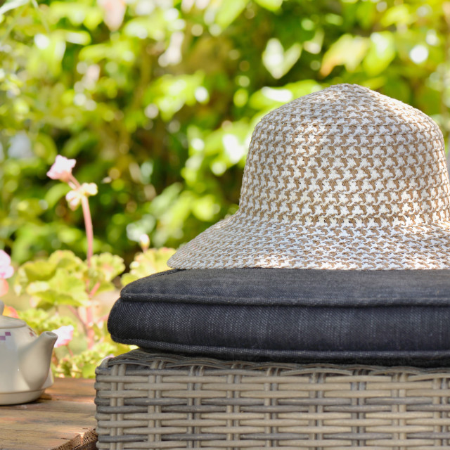 """""""close on braided hat put on a lounge chair next to wooden table"""" stock image"""