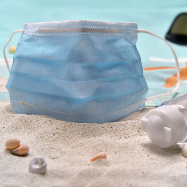 """""""close to blue surgical mask and hand sanitizer on the beach - concept vacation with"""" stock image"""