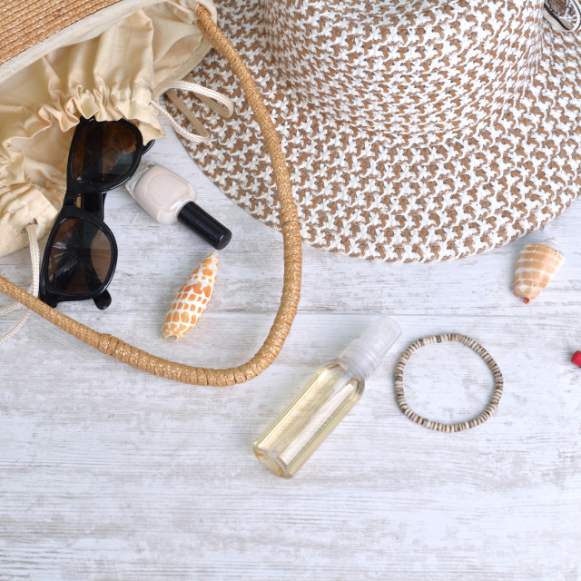 """""""hand bag and hat with female accessories spilled on white table"""" stock image"""