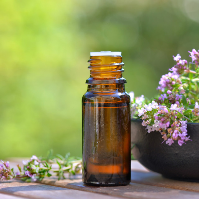 """""""bottle of essential oil and flowers of aromatic herb on a table on green background"""" stock image"""