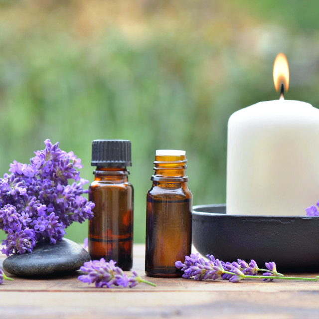 """""""bottles of essential oil among lavender flower arranged on a wooden table in garden with"""" stock image"""