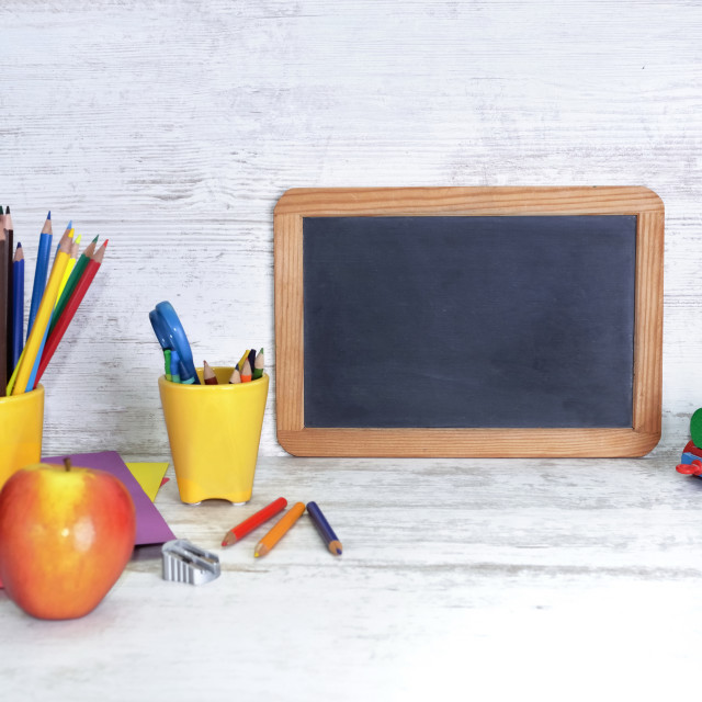 """black board on a kid desk with colorful pencils in yellow pot and toy abd apple"" stock image"