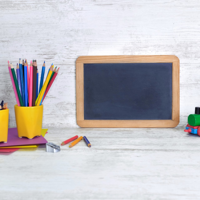 """slate on a kid desk with colorful pencils in yellow pot and a toy"" stock image"
