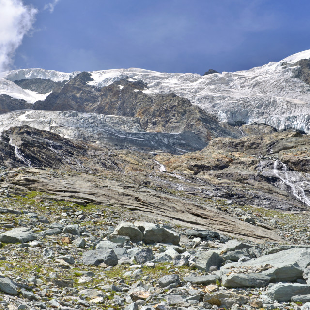 """hiker climbing rocky mountain to a glacier in summer"" stock image"