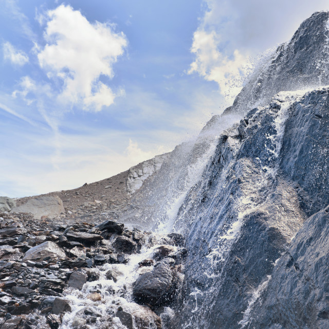 """close on water flowing from glacier on a rocky wall in alpine mountain"" stock image"