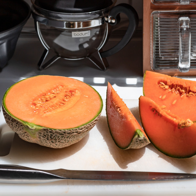 """Melon sliced on a white cutting board"" stock image"