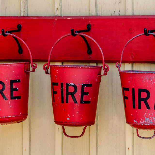 """""""Embsay and Bolton Abbey Steam Railway. Three Hanging Red Fire Buckets."""" stock image"""