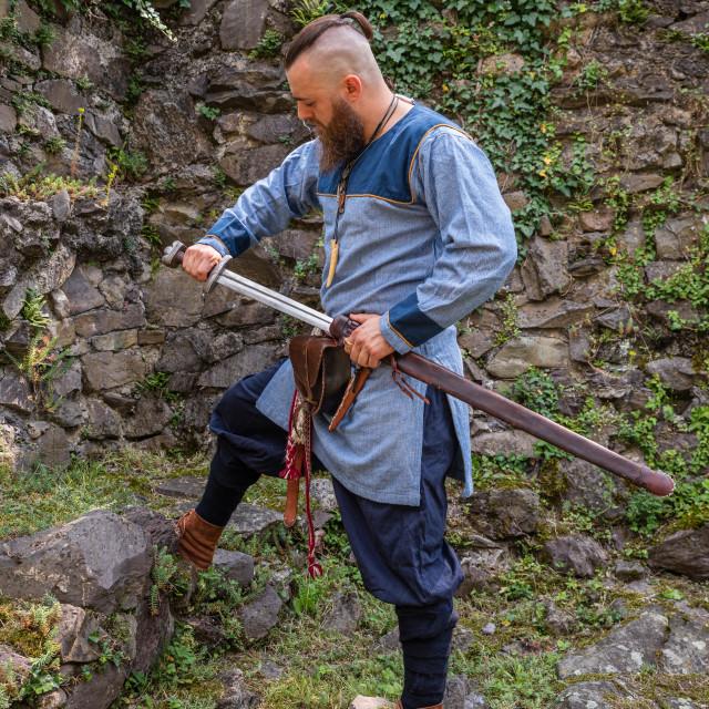 """Viking warrior draws his sword"" stock image"