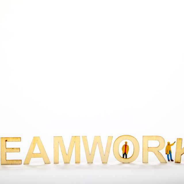 """Wooden teamwork sign with miniature figure workmen working together to complete the sign teamwork concept with copy space"" stock image"