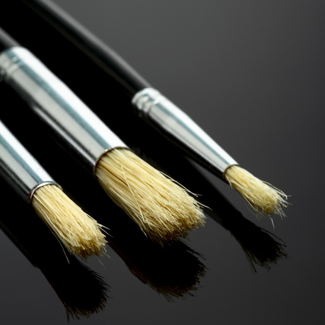 """selection of artists bristle paint brushes isolated on black glass"" stock image"