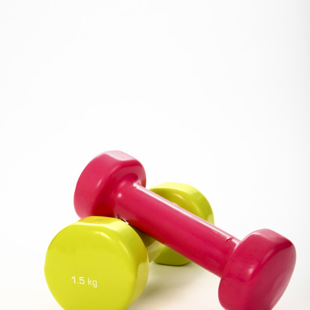 """Two weight training dumbbells isolated on a white background with copy space"" stock image"