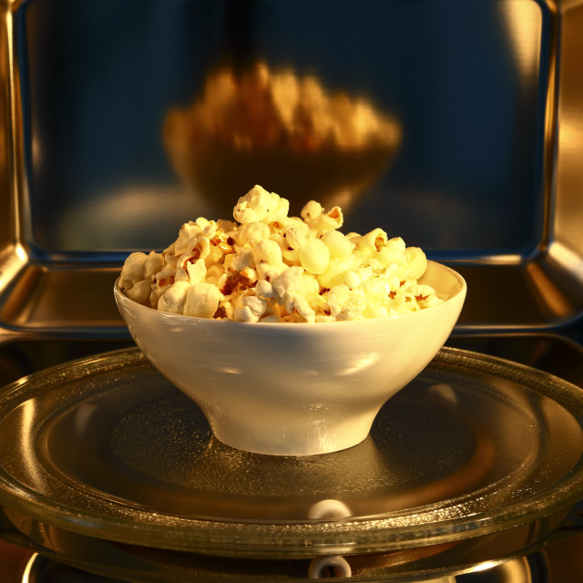"""Bowl of popcorn inside the cavity of a stainless steel microwave oven"" stock image"