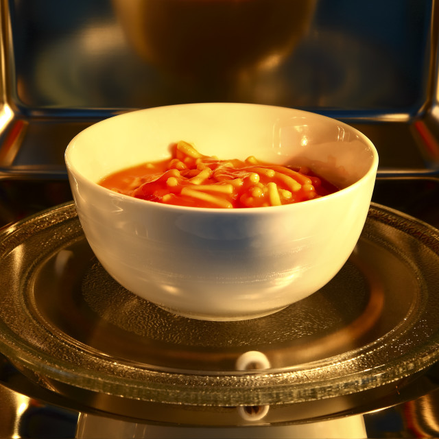 """Bowl of spaghetti pasta inside the cavity of a stainless steel microwave oven"" stock image"