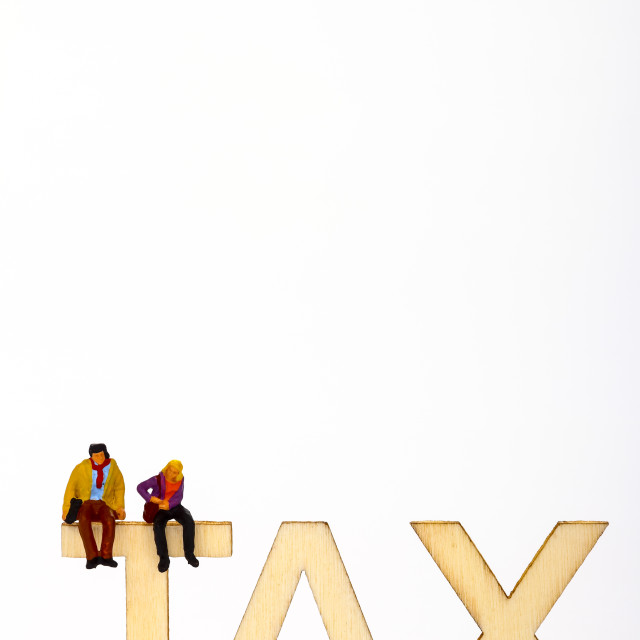 """Wooden tax sign with a miniature figure couple"" stock image"