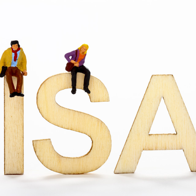 """Miniature figure couple sat on wooden ISA letters"" stock image"