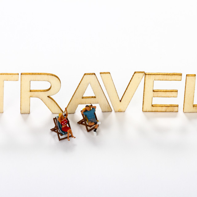 """Wooden travel sign with miniature figure people"" stock image"