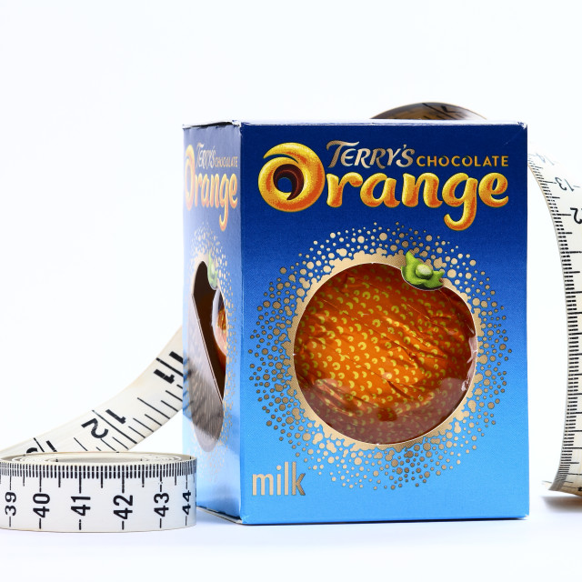 """Terrys chocolate orange manufactured by carambar & co with a tape measure can be used for shrinking size of products or calories"" stock image"