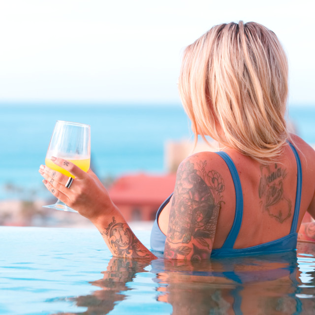 """""""Woman holding cocktail in swimming pool"""" stock image"""