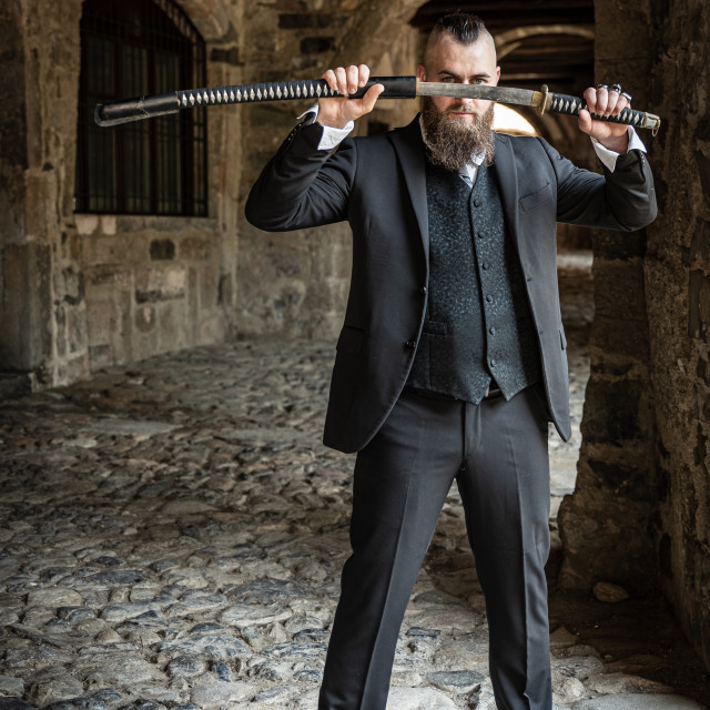 """""""A man in elegant clothes shows off his katana at eye level"""" stock image"""