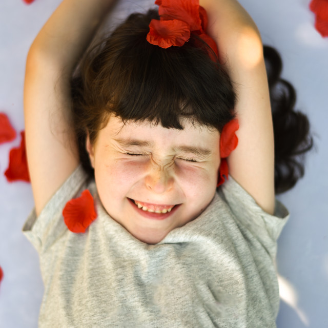 """""""Smiling little girl squints as rose petals fall on her"""" stock image"""