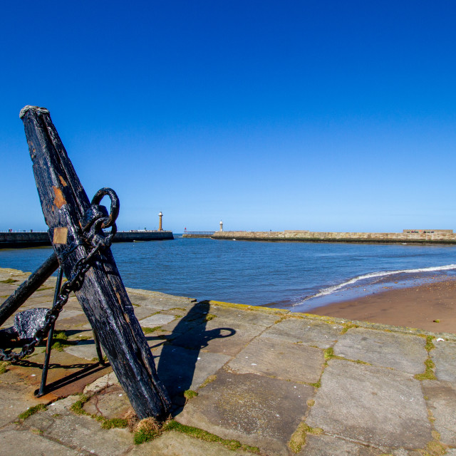 """""""Whitby,UK,Yorkshire,East coast, Old Anchor on Tate Hill Pier. Collier Hope Beach in the Background."""" stock image"""