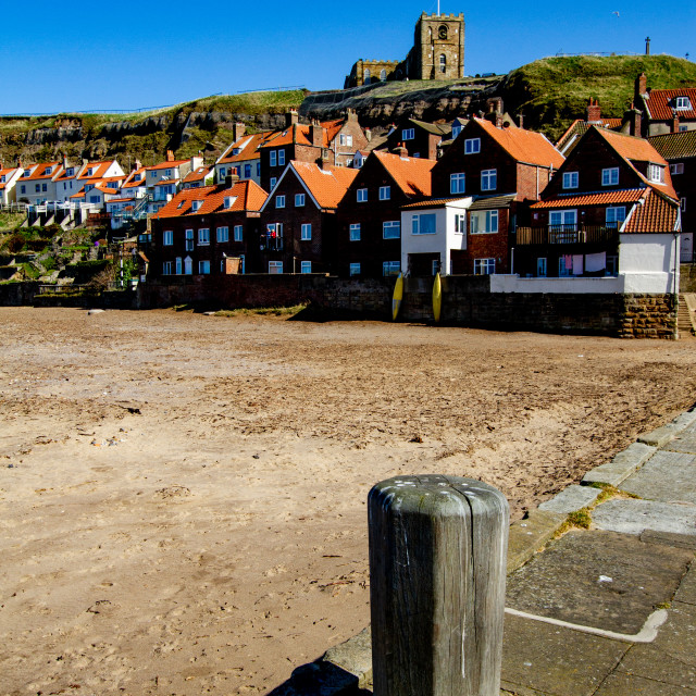 """""""Whitby,UK,Yorkshire,East coast, Mooring Post on Tate Hill Pier. Collier Hope Beach and St Mary's Church in the Background. Photographed April 2013."""" stock image"""