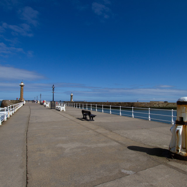 """""""Whitby,UK,Yorkshire,East coast, White Capstan on the Harbour Wall, Lighthouse in the Background."""" stock image"""