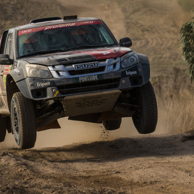 """An Isuzu Rodeo off-road race car makes a jump on a dirt road"" stock image"